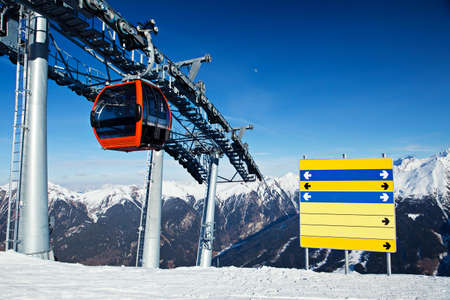 ski lift: Red gondola ski lift and blank direction board