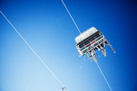 Ski lift carrying unrecognizable skiers up to the clear blue sky photo