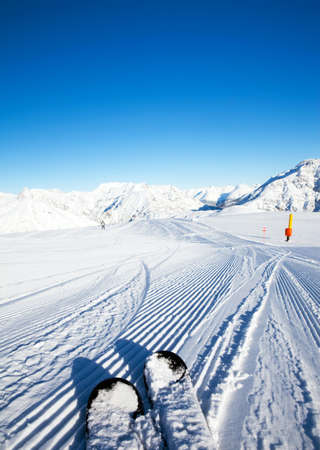 Fresh made ratrak (snowcat) snow curves under your skis and mountains panorama in the morning sunlight