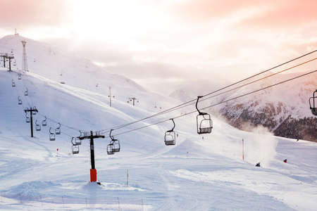 Winter mountains panorama with ski slopes and ski lifts on a cloudy day