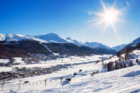 View down on typical Alpine ski resort and ski slopes, Livigno, Italy, Europe