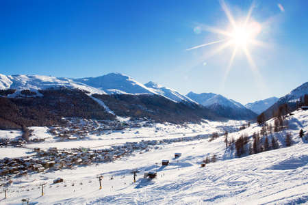 View down on typical Alpine ski resort and ski slopes, Livigno, Italy, Europe