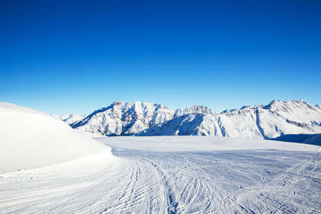 The view of winter mountains, covered with snow, ski slope on the foreground photo