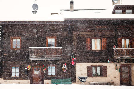 view of a wooden doorway: Snowing in front of tradition house facade