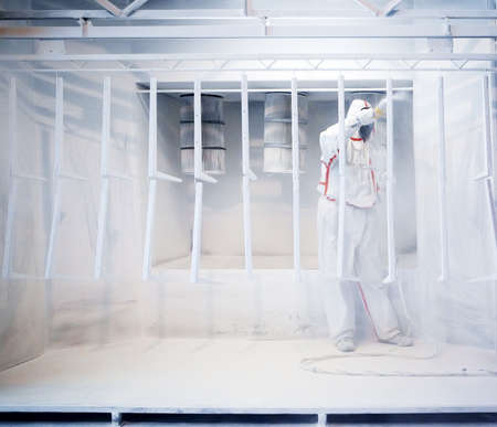 coating: Worker wearing protective wear performing powder coating