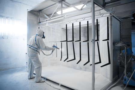 Operaio che indossa abbigliamento protettivo di eseguire verniciatura a polvere