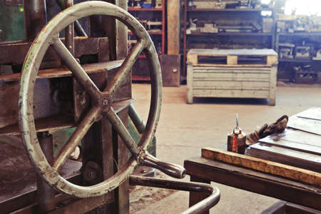 An old factory interior and a part of obsolete heavy machinery with control metal wheel Stock Photo - 12246392
