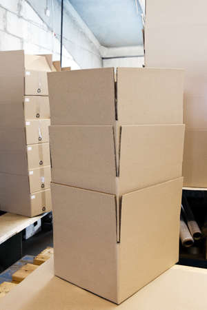 boxboard: A lot of various cardboard boxes arranged up in stacks at an industrial distribution storage room Stock Photo