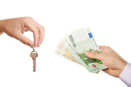 Concept of selling property - two businessmen hands giving each other modern key and cash money  Euro banknotes  while selling buying or letting renting real estate, isolated over white background photo