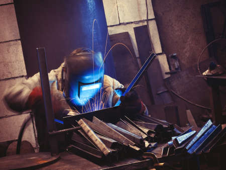 Worker wearing protective face mask using mig welding causing sparks flying over the working table while producing metal details
