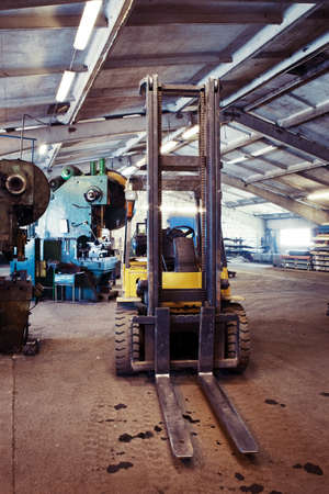 Fork lifter truck in the industrial interior of a small factory Stock Photo - 12591455