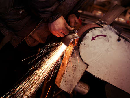 amateur: Amateur worker at the workshop keeping a metal plate in his hands and grinding it on grinder, causing many sparks