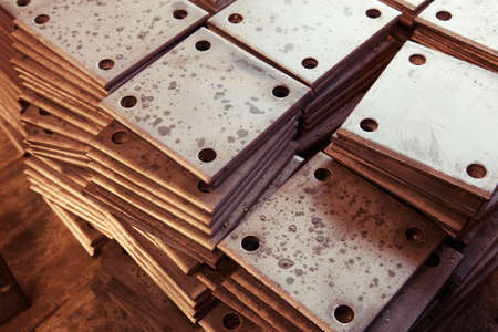 Grunge rusty rectangle metal plates with round holes placed on wooden textured board   photo
