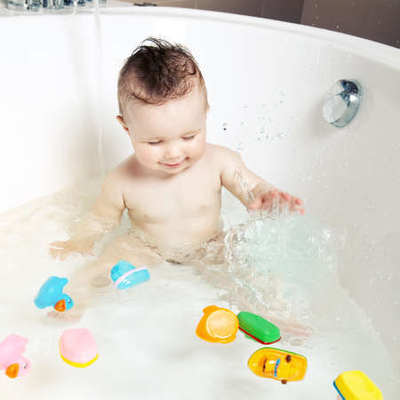 Cute smiling baby having fun and splashing water while taking a bath  Stock Photo