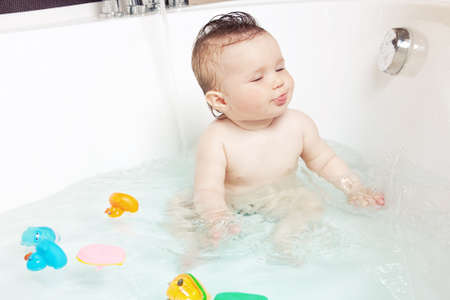 Cute baby playing with water and showing tongue while taking a bath photo