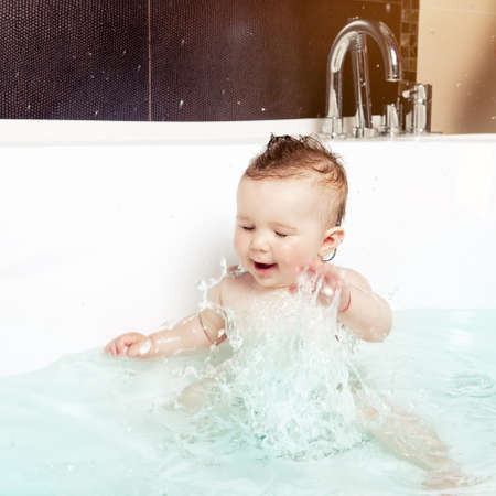 Cute baby having fun, splashing water and laughing while taking a bath in a modern bathroom interior photo