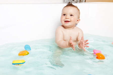 bathing beauty: Cute baby clapping hands and smiling while taking a bath