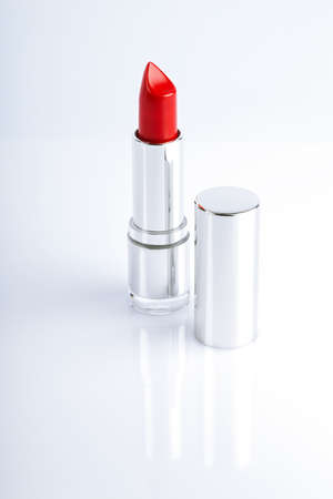 Red lipstick in silver metal tube over white reflective background photo