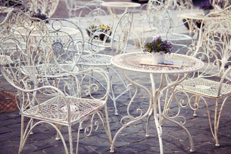 Lavender on the white metal table and ornate chairs in Provence style street cafe photo