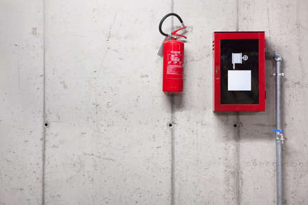 evacuacion: Un extintor de incendios y una manguera de incendios en la pared de hormig�n
