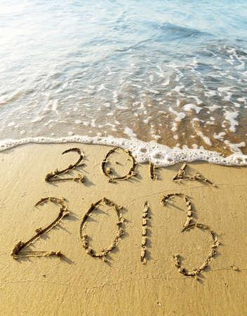 inscription 2012 and 2013 on a beach sand