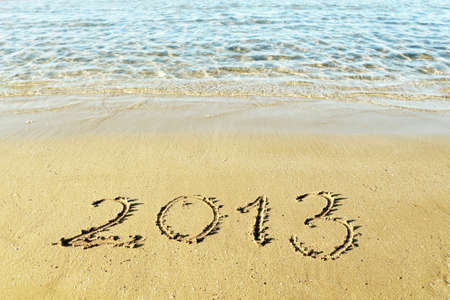 New Year is coming concept - the inscription 2013 on a beach sand photo