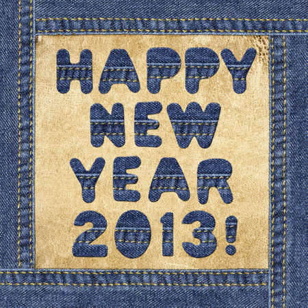 Holiday greeting - Happy New Year 2013! - made of denim letters in jeans frame on a leather label photo