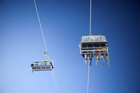 Ski lift carrying skiers up in the clear blue sky  photo