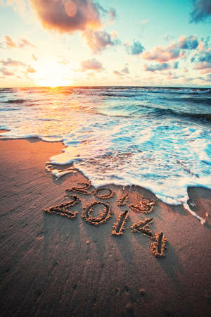New Year 2014 is coming concept - inscription 2013 and 2014 on a beach sand, the wave is covering numbers 2013  Stock Photo