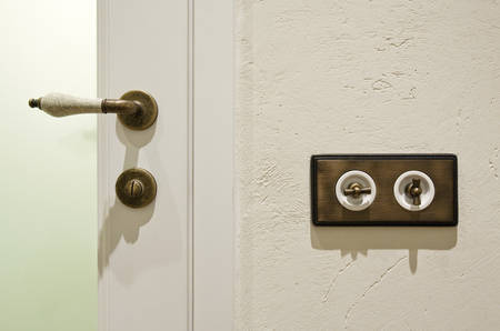 Stylish vintage brass light switchers on textured white wall and china door knob, the elements of interior photo