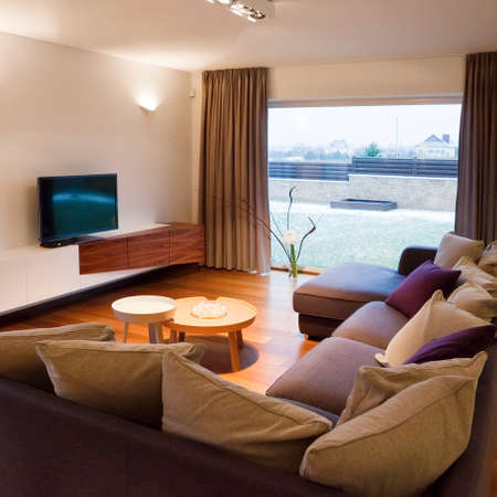 view of a spacious living room: Interior design - cozy living room with TV set and large window  Stock Photo