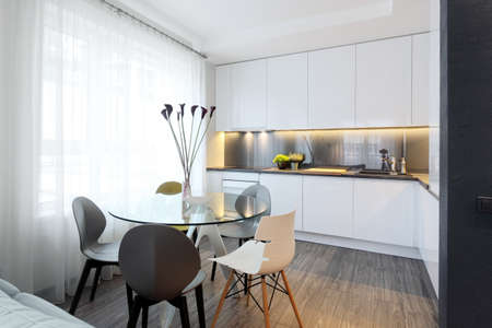 table glass: Interior - white modern kitchen and a glass dining table with chairs