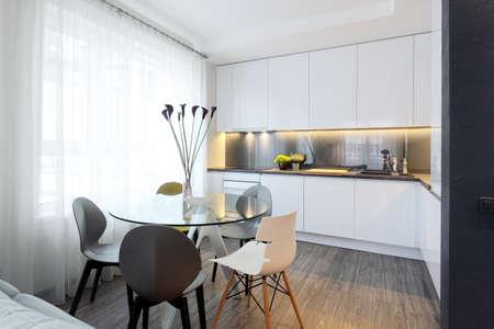 Intérieur - cuisine moderne blanc et une table à manger en verre avec des chaises
