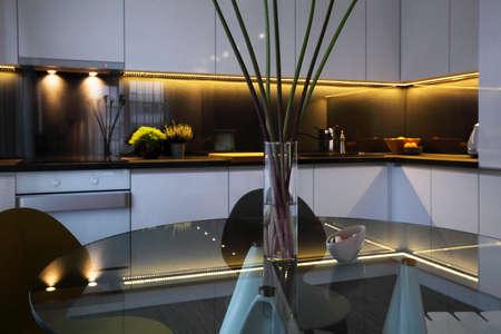 Interieur - witte moderne keuken en een glazen eettafel met stoelen