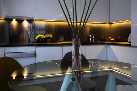 dining table and chairs: Interior - white modern kitchen and a glass dining table with chairs