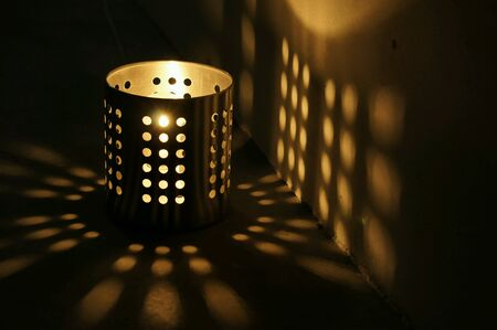 glow: Candle shining through a tin holder with shadow casted on wall and table