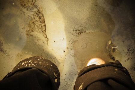 Feet dipped in muddy beach water