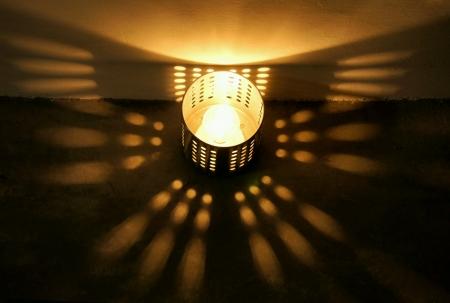 cilinder: Light bulb in a metal cilinder casting shadow