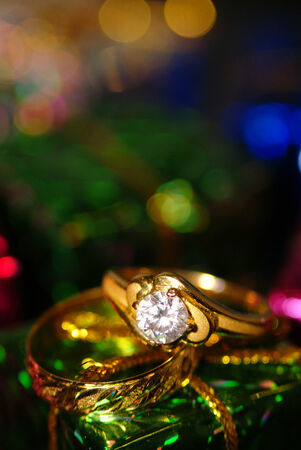 Gold solitaire wedding rings with diamond close up on shiny box photo