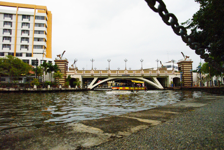 sight seeing: Ferry carrying passenger underneath Hang Tuah Bridge