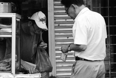 Adult man buying fried breadstick  cakoi  from a street vendor