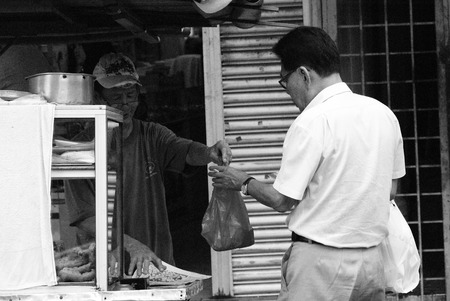 sight seeing: Adult man buying fried breadstick  cakoi  from a street vendor