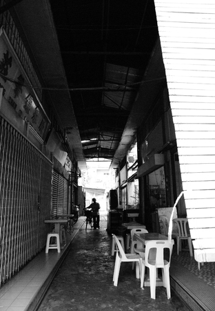 View of an alley in between buildings at Malacca Town with an old man pushing his bicycle