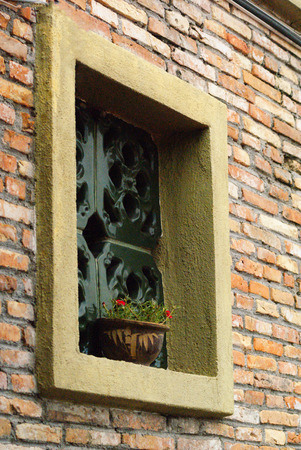 red brick repetition: Window with a flower pot on red brick wall Stock Photo