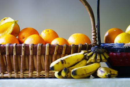 Tropical fruits in basket - banana, oranges, starfruit
