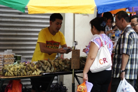 Young Chinese man selling traditional rice dumplings and pineapple tarts at roadside hawker stand