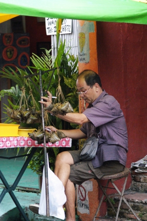 An old Chinese man selling traditional rice dumplings at roadside hawker stand