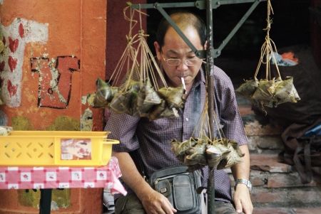 roadside stand: An old Chinese man selling traditional rice dumplings at roadside hawker stand Editorial