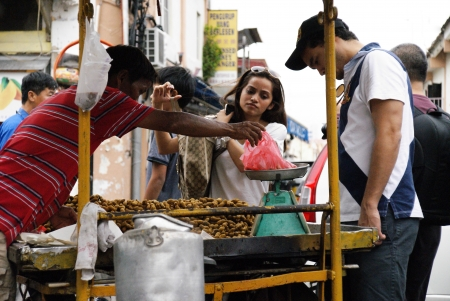 Asian man selling boiled peanuts at roadside hawker stand