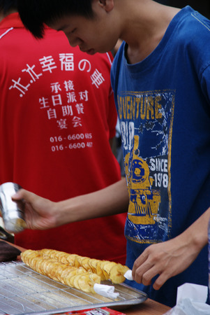 roadside stand: Young Asian teenager selling sliced baked potato at roadside hawker stand